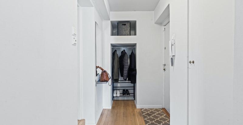 Det første som møter deg er en romslig entré med dørcalling med åpner og praktisk bod/kott og en nisje med garderobe. Her har man god plass til å henge i fra seg tøy
