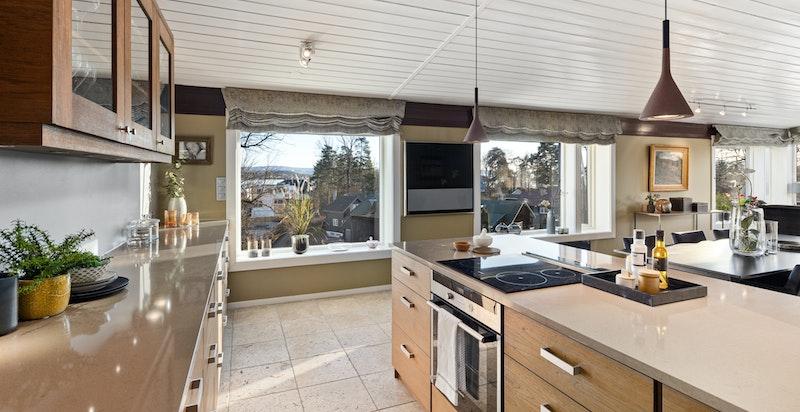 Velutstyrt kjøkken med snekkerbygget innredning i teak og benkeplate i sten