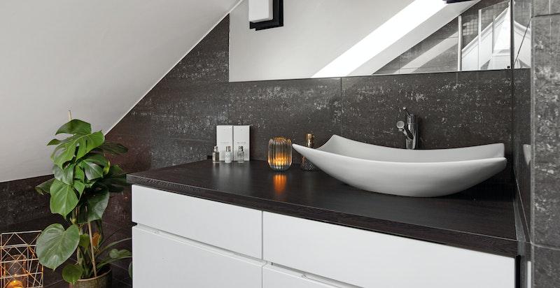 Vegghengt innredning med skuffer og toppmontert servantskål. Innfelt speil i vegg over servant med belysning