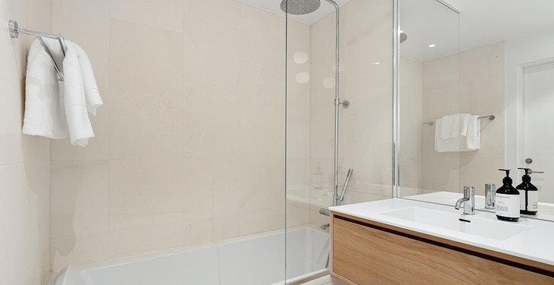 Bad ensuite med badekar, vegghengt wc, innebygget skap i vegg samt servantskap
