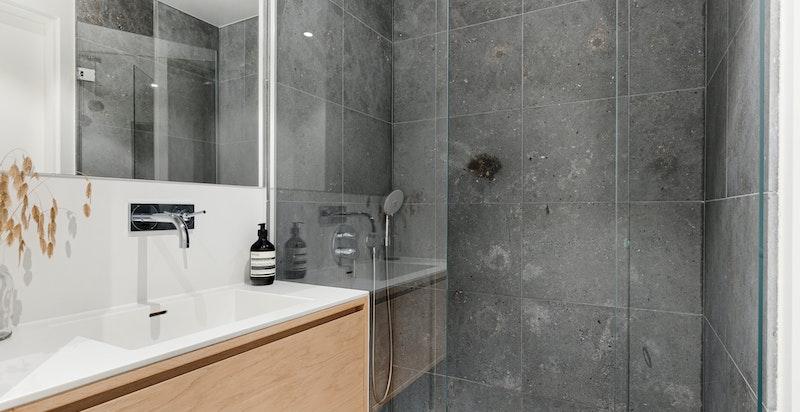 Meget pent gjestebad med romslig dusjnisje og servat med servantskap. Fin og praktisk belysning