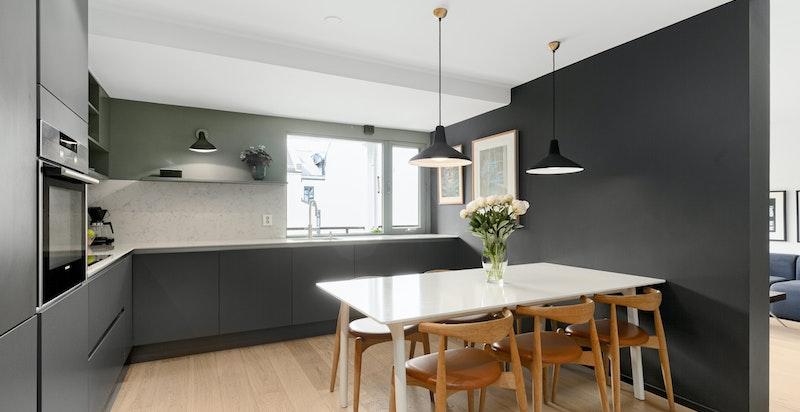 Stilrent kjøkken med spiseplass og snekkerbygget oppbevaringsseksjon