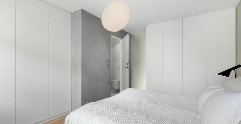 To vegger med garderobeskap fra gulv til tak. Bad ensuite. Praktisk og privat del av leiligheten