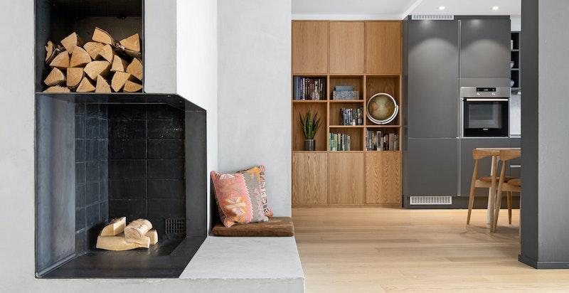 Herlig åpen peis er en lunende og kompletterende detalj i rommet og kan nytes fra benken som er murt opp ved siden av, fra stuen eller kjøkkenet