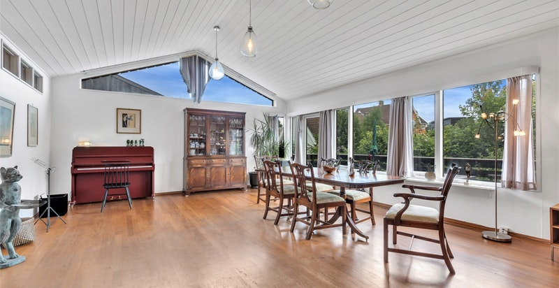 Stor, åpen stue med god takhøyde og store vindusflater