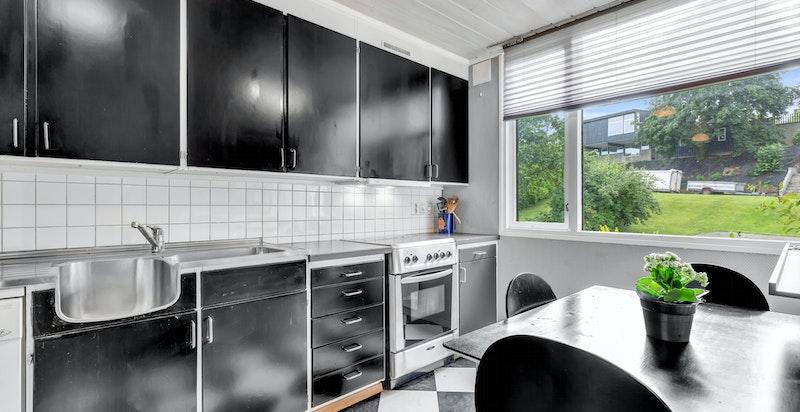 Hyggelig spiseplass på kjøkken med morgenlys og utsyn mot grøntområde