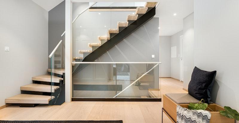Romslig mellomgang med garderobeløsning - lekker trapp forbinder etasjene