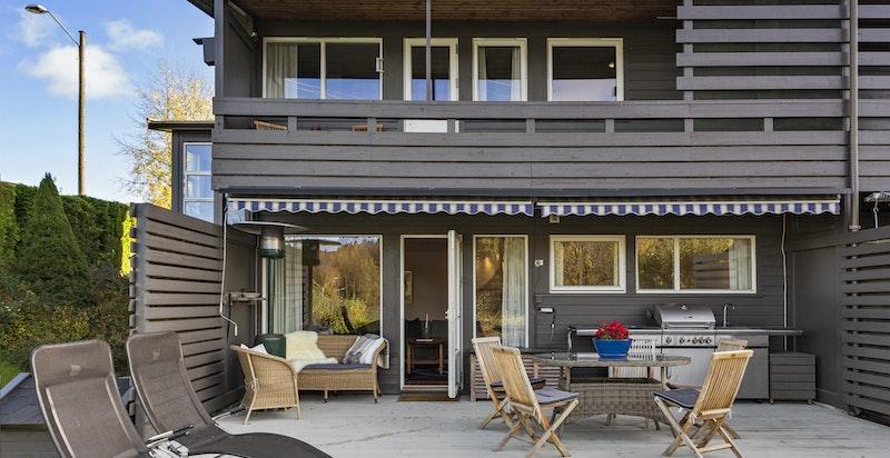 Terrasse mot vest - plass både til sittegrupper og spisebord. Utekjøkken med grill.