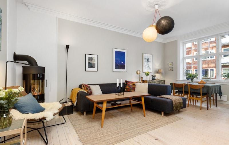 Luftig stue med moderne peis og store vindusflater