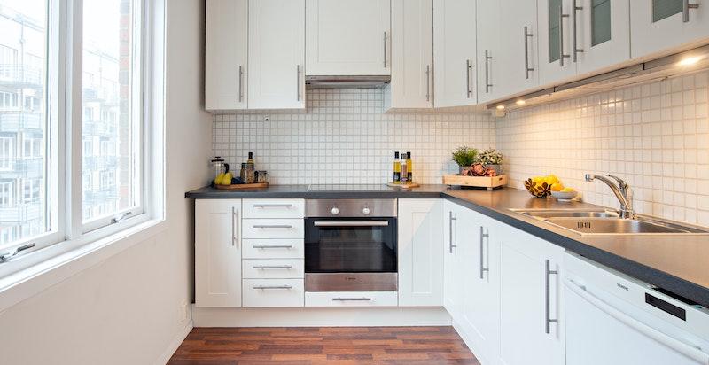 Separat kjøkken med hvit innredning.