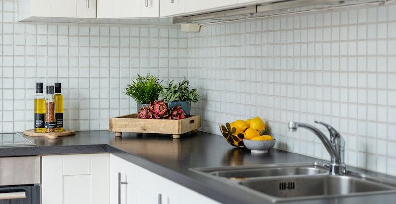 Hvite mosaikkfliser på vegg mellom benk og overskap. Benkeplate i laminat.