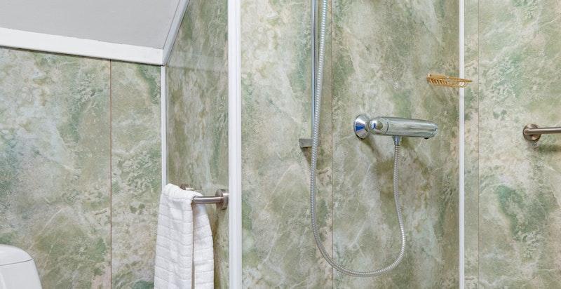 Dette badet er innredet med dusj, servantskap og toalett