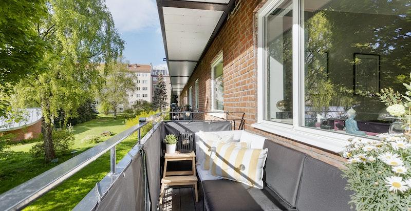Solrik balkong mot frodig gårdsrom
