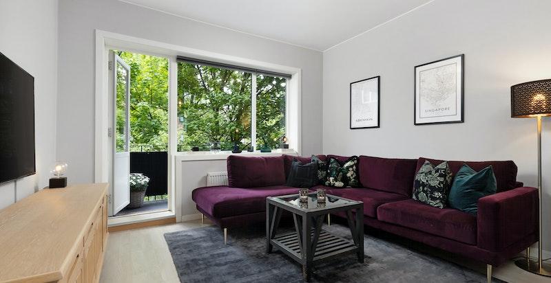 Stue med store vindusflater og utgang til balkong