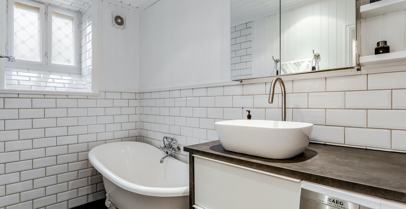 Badet er innredet med badekar med løveføtter, metrofliser på veggene og veggmontert dusj.