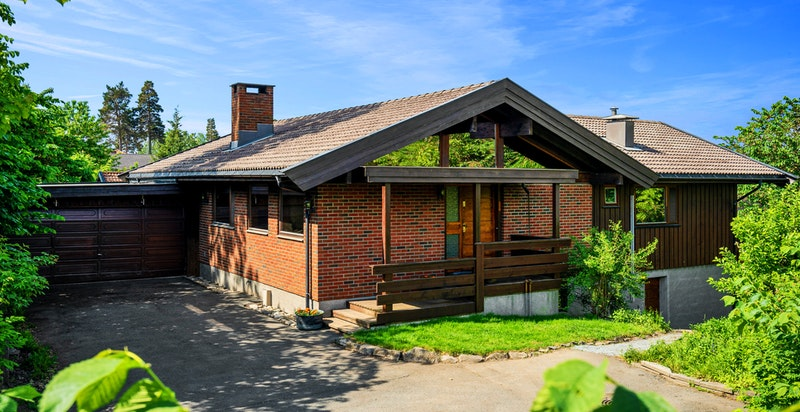 Fasade med gårdsplass og garasje