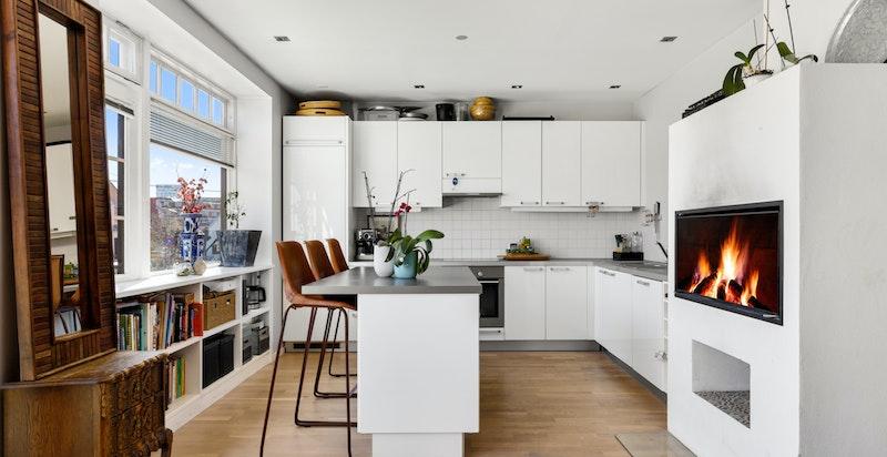 Lekkert moderne kjøkken med kjøkkenøy og peis