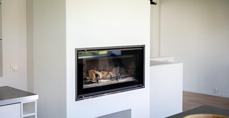 Strategisk godt plassert peis kan nytes fra både stue og kjøkken