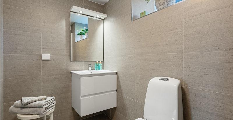 Badet er innredet med servantskap, speil, toalett og dusj m/innfellbare glassdører