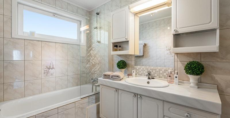 Badet er innredet med stort servantskap, innfliset badekar og toalett