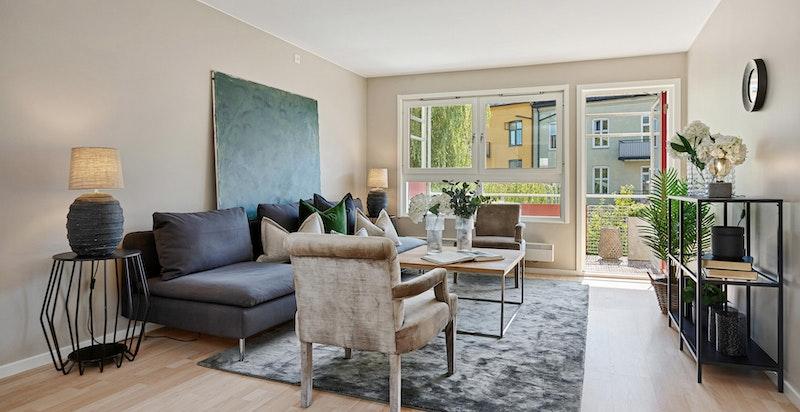 Luftig stue med store vindusflater og utgang til balkong