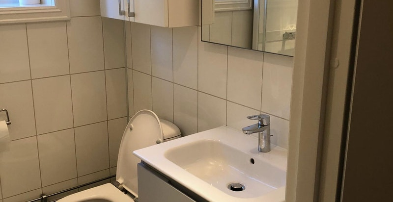 Flislagt bad med varmekabler i gulv. Opplegg til vaskemaskin.