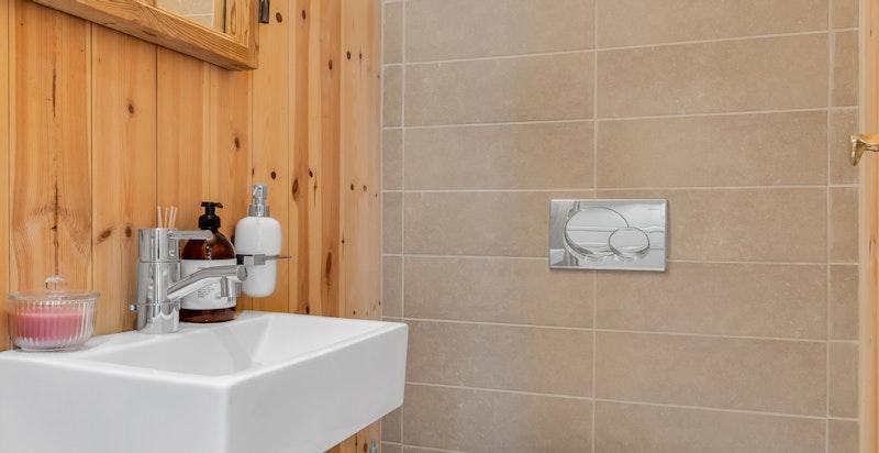 Separat toalettrom bygget i 2010. Rommet inneholder veggmontert toalett og veggmontert servant med blandebatteri