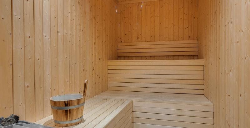 Badstue med sluk i gulv, elektrisk ovn, panel og benker i treverk uten synlige skruer