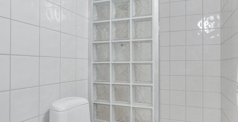 Dusjbadet innenfor hovedsoverommet inneholder dusjhjørne med glassbyggerstein, toalett, søyleservant og blandebatteri