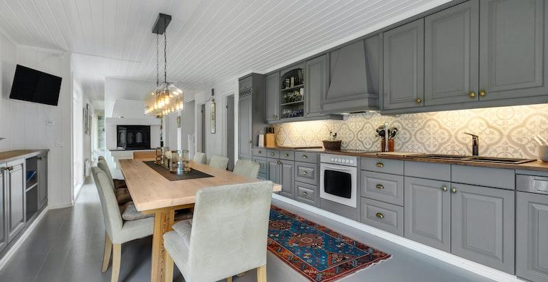 Kjøkkeninnredning består av malte profilerte fronter med stålhåndtak, heltre benkeplater, sort antrasitt kummer med blandebatteri, fliser over benk, lys under overskap, integrerte hvitevarer