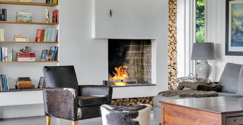 Stue i hoveddelen med hyggelig peis og direkte utgang til platting og hage