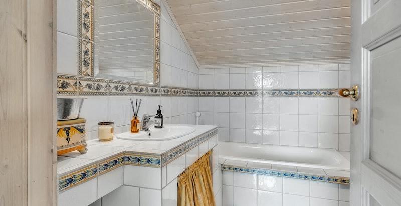 Baderom med innmurt badekar, toalett, servant med blandebatteri