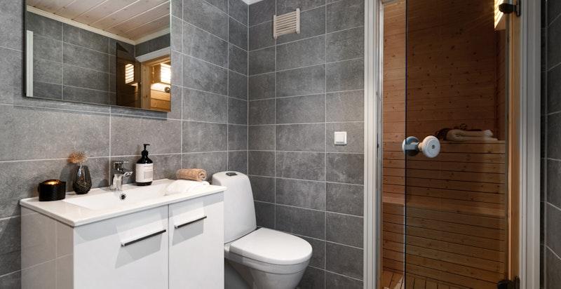 Badet er innredet med servantskap, toalett og servantskap med speil