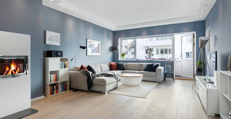 Stor stue med spisestuedel og nyere peis med innsats. Downlights langs veggene gir lun belysning