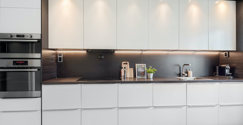God arbeidssone på kjøkkenet. Innfelt belysning i tak og under skap sikrer godt arbeidslys