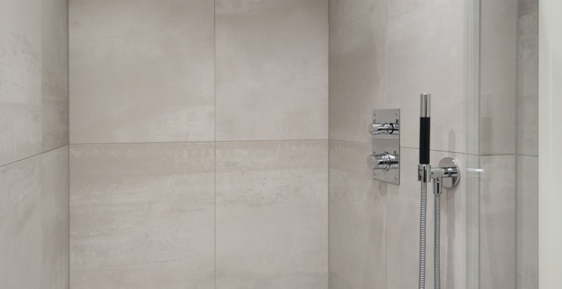 Romslig dusjnisje med regnfallsdusj, vanlig dusj og glassvegg