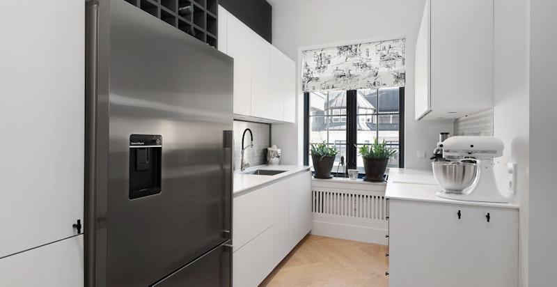 Grovkjøkken med stort kjøl og fryseskap med isdispenser ekstra oppvaskmaskin og vask samt rikelig med skap og benkeplass
