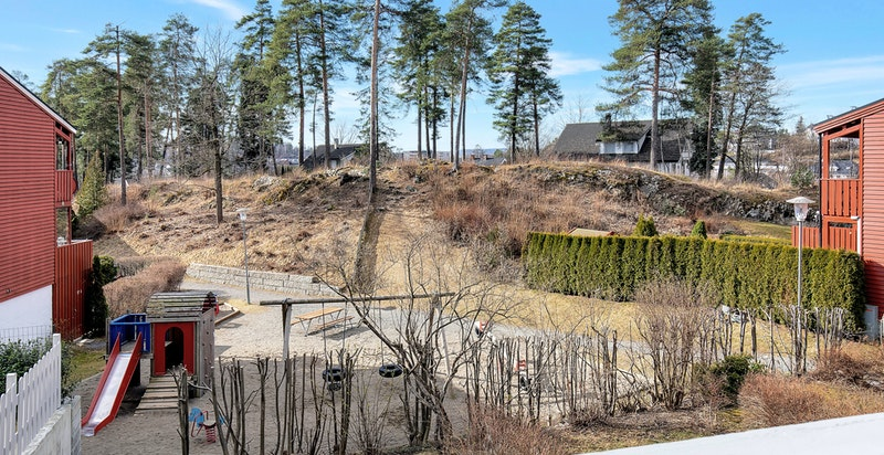 Fritt utsyn til hage, lekeplass og sameiets egen skog fra hovedbalkongen. Ingen innsyn
