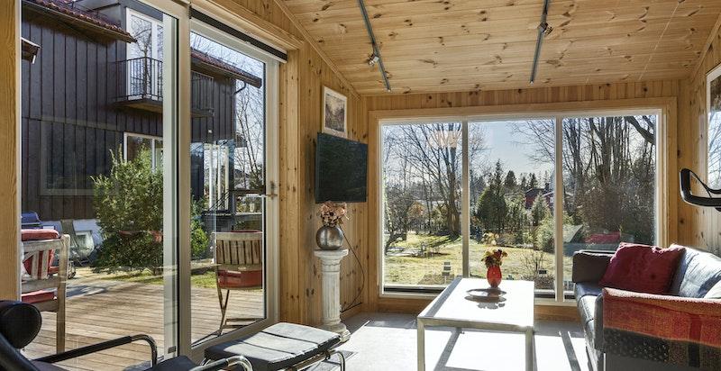 """""""Stue"""" i atelier, innenfor garasjen med store vinduer mot hagen og dør ut til sjermet solrik terrasse"""