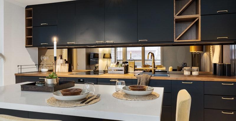 Køkkeninnredning (2018) fra IKEA med glatte sorte fronter på skuffer og skap. Speilglass på vegg mellom benk og overskap.
