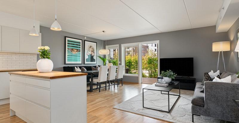 Romslig innholdsrik stue med plass for stor salong, stort spisebord og åpen løsning til kjøkken adskilt med kjøkkenøy