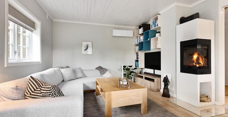 Hyggelig stue med spiseplass og nyere peis med glass på to sider