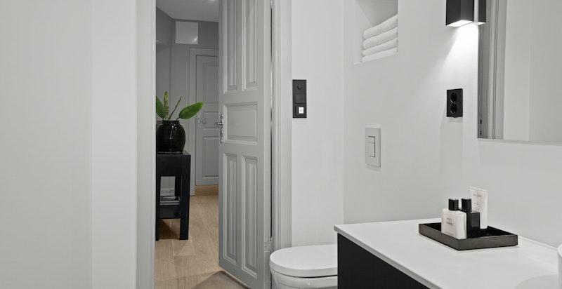 Hovedbad med vegghengt wc med innebygget sisterne og hylle. Varmekabler i gulv og downlights i himling.