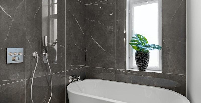 Våtsone med dusj og badekar innerst i rommet. Naturlig lys med vindu.