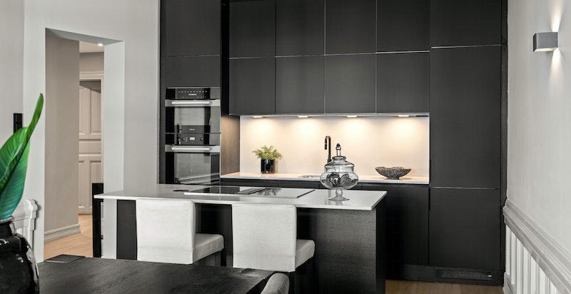Stort spisekjøkken med integrert kjøkkenøy.