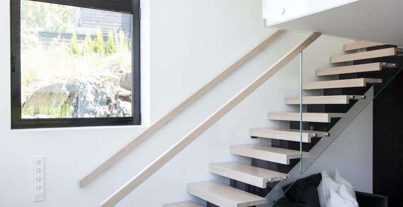 Trapp i stålkonstruksjon med eiketrinn og glassrekkverk