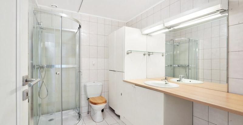 Bad med dusjkabinett, toalett og servant med underskap.