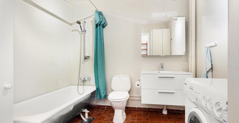 Eldre bad med nyere innredning, badekar og opplegg til vaskemaskin/tørketrommel.
