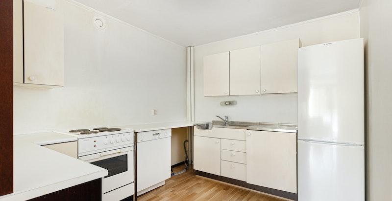 Kjøkkenet er utstyrt med  hvite glatte fronter, laminat benkeplate, rustfritt benkebeslag, nisje for kjøleskap, komfyr og oppvaskmaskin.