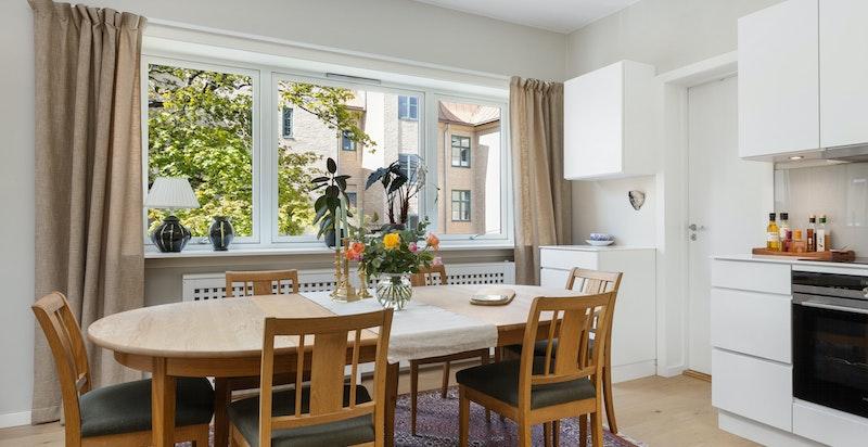 Hyggelig spiseplass ved kjøkkenet og det store vinduet med grønt utsyn